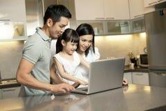 Famille asiatique dans la cuisine avec un ordinateur portatif Photo stock
