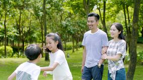 Famille asiatique de 4 marchant et riant en parc en été ensoleillé dans le mouvement lent clips vidéos