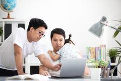 Famille asiatique et petite fille, alors que le papa travaille avec le carnet sur W Images libres de droits