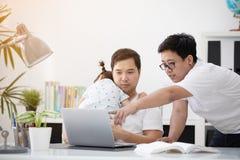 Famille asiatique et petite fille, alors que le papa travaille avec le carnet sur W Image libre de droits
