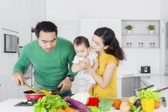 Famille asiatique faisant cuire le légume Images libres de droits