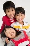 Famille asiatique heureuse étreignant sur le fond gris Images libres de droits