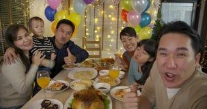 Famille asiatique heureuse prenant la photo de selfie à une fête de Noël banque de vidéos
