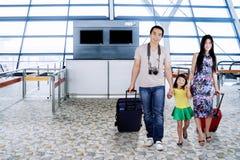Famille asiatique marchant ensemble sur l'aéroport Image libre de droits