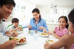 Famille asiatique s'asseyant au Tableau mangeant le repas ensemble image libre de droits