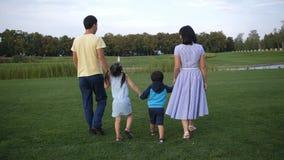 Famille asiatique tenant des mains et marchant dehors banque de vidéos