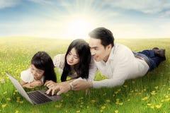 Famille attirante avec l'ordinateur portable en nature Image libre de droits