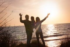 Famille au coucher du soleil par la mer Photographie stock libre de droits