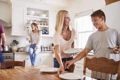 Famille avec des adolescents étendant le Tableau pour le repas dans la cuisine image stock