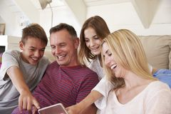 Famille avec des adolescents s'asseyant sur Sofa Looking At Mobile Phone à la maison photo libre de droits