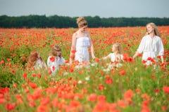 Famille avec des amis dans le domaine rouge de pavot Photographie stock