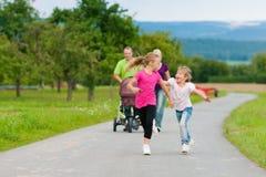 Famille avec des enfants ayant la promenade Image libre de droits