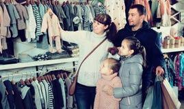 Famille avec des enfants choisissant des vêtements pour nouveau-né Photographie stock libre de droits