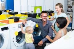 Famille avec des enfants choisissant la machine à laver Image libre de droits