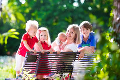 Famille avec des enfants détendant sur un banc de parc Image stock