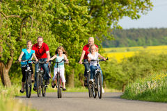 Famille avec des enfants faisant un cycle en été avec des bicyclettes Image libre de droits