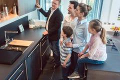Famille avec des enfants regardant une cuisine dans la salle d'exposition photo stock