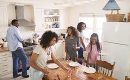 Famille avec des filles adolescentes étendant le Tableau pour le repas dans la cuisine photo libre de droits