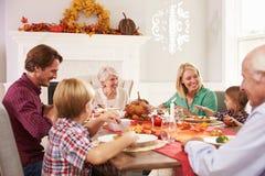 Famille avec des grands-parents appréciant le repas de thanksgiving au Tableau image libre de droits