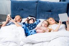 famille avec deux enfants à l'aide des dispositifs numériques tout en se trouvant ensemble images stock