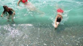 Famille, avec deux enfants, un frère et des soeurs éclaboussant dans les vagues de l'océan sur le rivage Ils attrapent la vague banque de vidéos