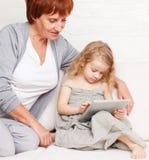 Famille avec l'ordinateur de comprimé au sofa Image libre de droits