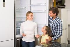 Famille avec la fille choisissant le grand réfrigérateur Image libre de droits