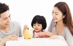 Famille avec la fille mettant des pièces de monnaie dans la tirelire Images stock