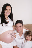 Famille avec la mère enceinte détendant sur Sofa Together avec W Images libres de droits