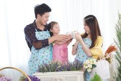 Famille avec la petite fille dans le jardin, temps de café Photographie stock libre de droits