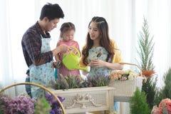 Famille avec la petite fille dans le jardinage de jeu Image stock