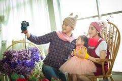 Famille avec la petite fille en parc prenant le selfie par l'appareil-photo Photos libres de droits