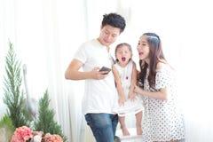 Famille avec la petite fille en parc prenant le selfie par le téléphone portable Photo stock