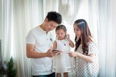 Famille avec la petite fille en parc prenant le selfie par le téléphone portable Images stock