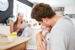 Famille avec la Tablette de Digital d'utilisation de bébé au Tableau de petit déjeuner Photo libre de droits