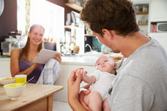 Famille avec la Tablette de Digital d'utilisation de bébé au Tableau de petit déjeuner Image stock