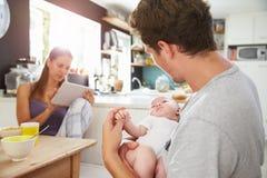 Famille avec la Tablette de Digital d'utilisation de bébé au Tableau de petit déjeuner Photographie stock