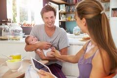 Famille avec la Tablette de Digital d'utilisation de bébé au Tableau de petit déjeuner Photo stock
