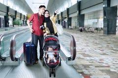 Famille avec le bébé se tenant dans le hall d'aéroport Image libre de droits