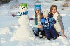Famille avec le bonhomme de neige Image stock
