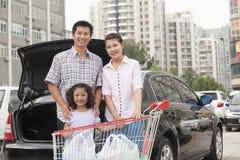 Famille avec le caddie se tenant à côté de la voiture Image libre de droits