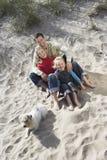 Famille avec le chien détendant sur Sandy Beach Photographie stock