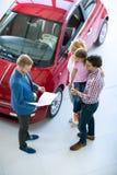 Famille avec le concessionnaire automobile dans la salle de concessionnaire automobile images libres de droits