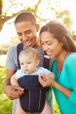 Famille avec le fils de bébé dans le transporteur marchant par le parc Photos stock