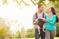 Famille avec le fils de bébé dans le transporteur marchant par le parc Photos libres de droits