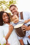 Famille avec le fils de bébé dans le transporteur marchant par le parc Photographie stock