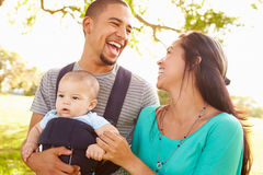 Famille avec le fils de bébé dans le transporteur marchant par le parc Photo libre de droits