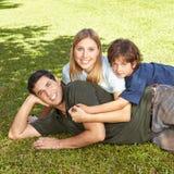 Famille avec le fils s'étendant dans l'herbe Photos libres de droits