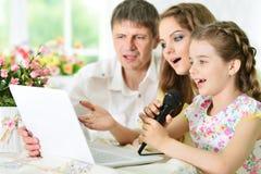 Famille avec le karaoke de chant d'ordinateur portable Photo stock