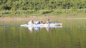 Famille avec le petit canoë de bébé sur une rivière calme clips vidéos